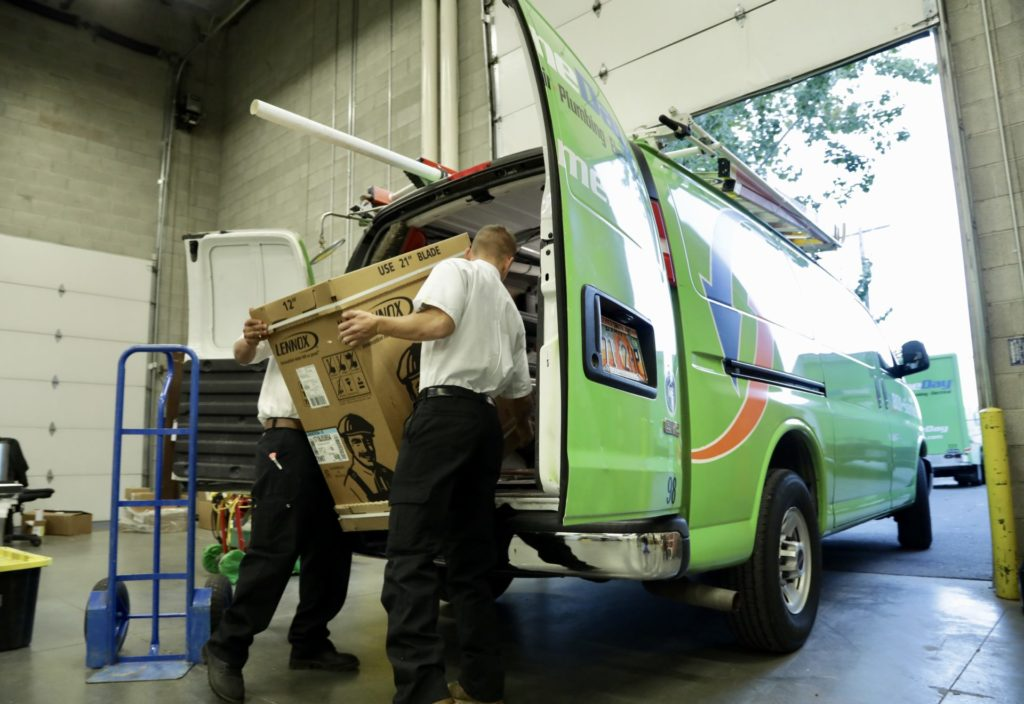 technicians loading an air conditioning unit into the back of a service van